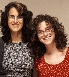 Two women, mother and daughter with long hair and glasses