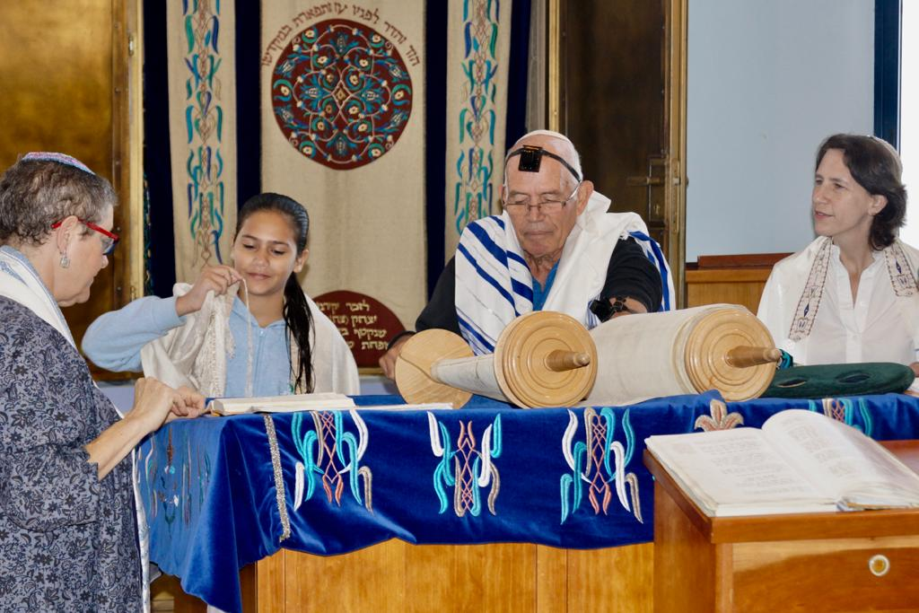 Girl blessing the Torah surround by two women and a man
